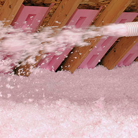 pink LooseFill blown-in fiberglass insulation being installed in a home attic