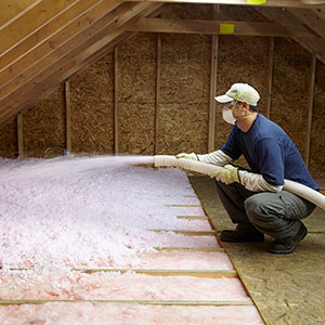 photo of a worker installing blown-in fiberglass insulation over batt fiberglass insulation in a new home attic
